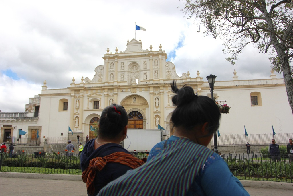 In this photograph taken Dec. 14, 2016, two indigenous women stroll through the central plaza of Antigua Guatemala, Guatemala, with the...