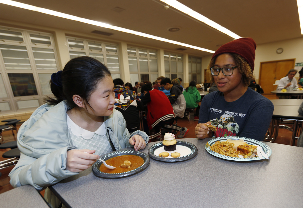 In this Jan. 27, 2017 photo, foreign exchange student Miaofan Chen, left, of Hefei, China, chats with Thandi Glick during a potluck mea...