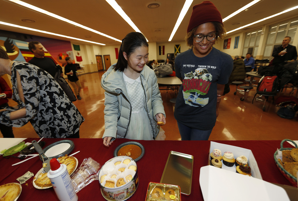 In this Jan. 27, 2017 photo, Miaofan Chen, left, works her way through the serving line with Thandi Glick during a potluck meal for Chi...