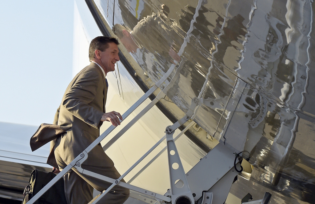In this Feb. 12, 2017, photo, National Security Adviser Michael Flynn boards Air Force One at Palm Beach International Airport in West ...