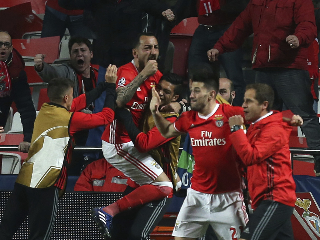 Benfica's Kostas Mitroglou celebrates with teammates scoring the opening goal during the Champions League round of 16, first leg, socce...