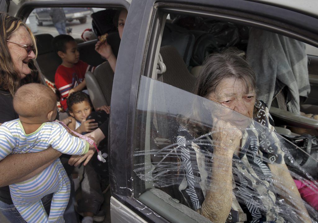 In this photo taken Monday, Feb. 13, 2017, Gerldeen Trammell, right, sits in her family's car with her daughter and grandchildren from ...