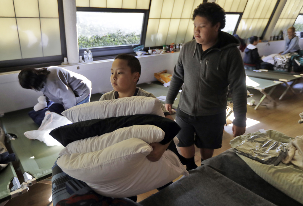 Rylan Moua, left, and his uncle Christopher Vang, right, of Oroville, Calif., gather pillows as they leave a shelter Tuesday, Feb. 14, ...