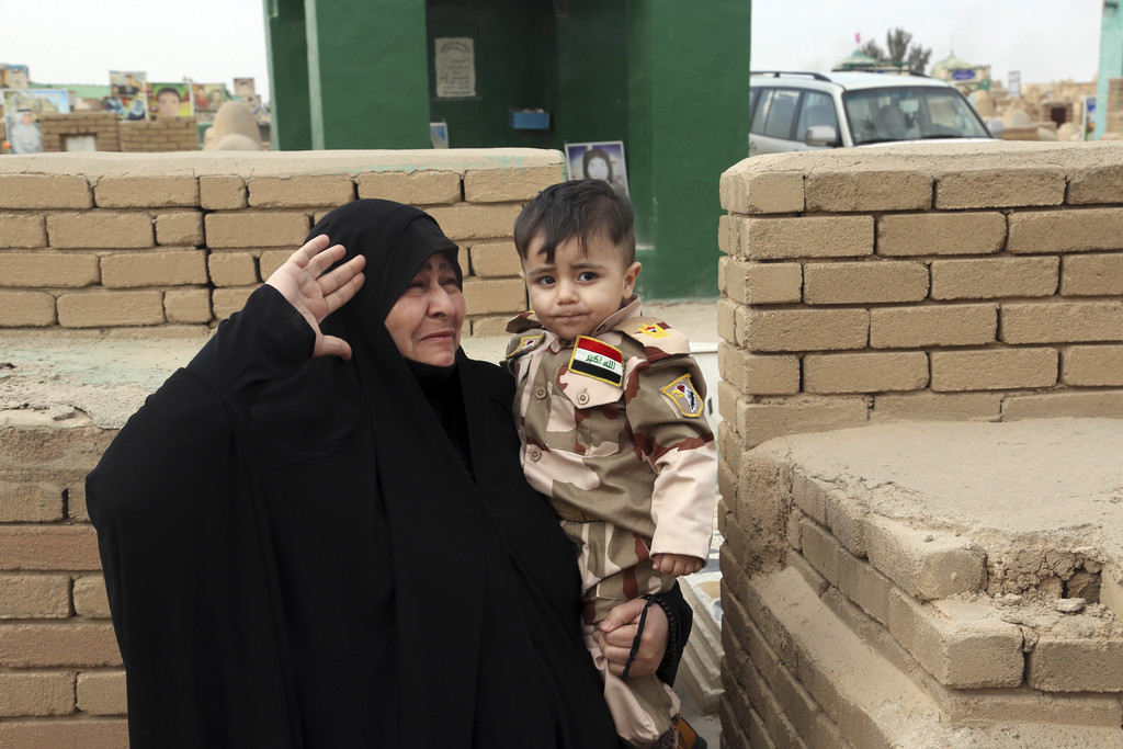 In this Wednesday, Feb. 15, 2017, the widow of Hamza Finjan, who was killed fighting Islamic State militants in Mosul, holds their son ...