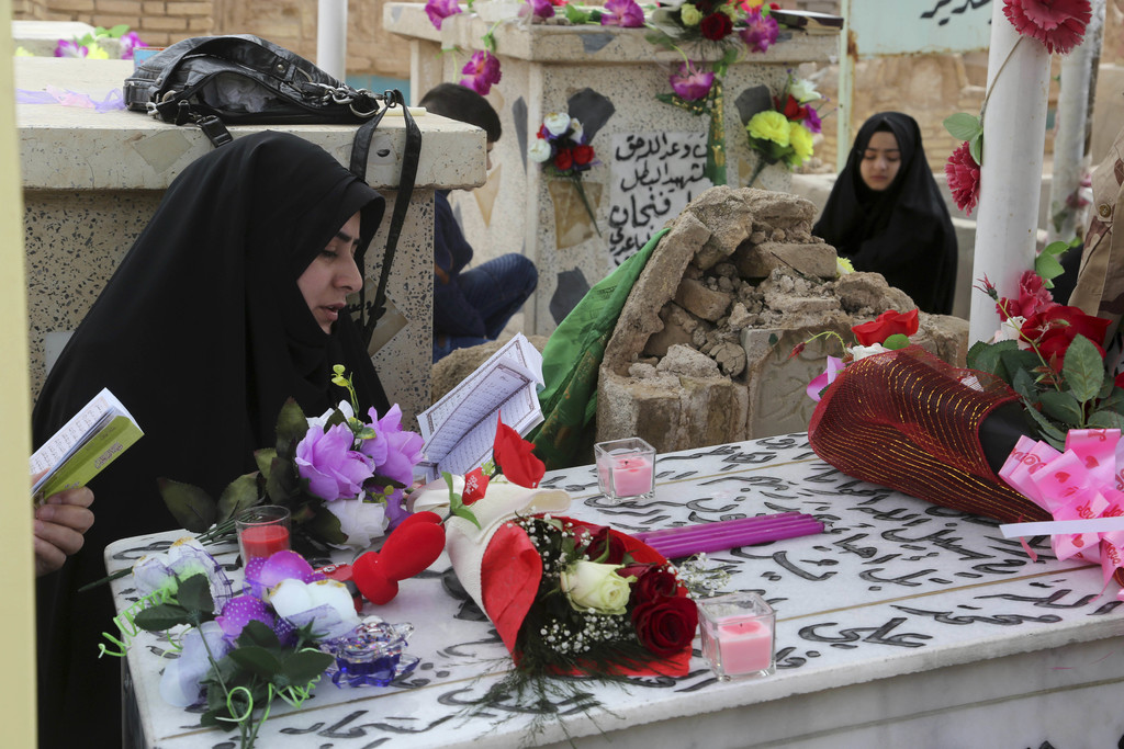 """In this Wednesday, Feb. 15, 2017 photo, family members of Iraqi Army officer, Hamza Finjan, pray over his grave in Wadi al-Salam, or """"V..."""