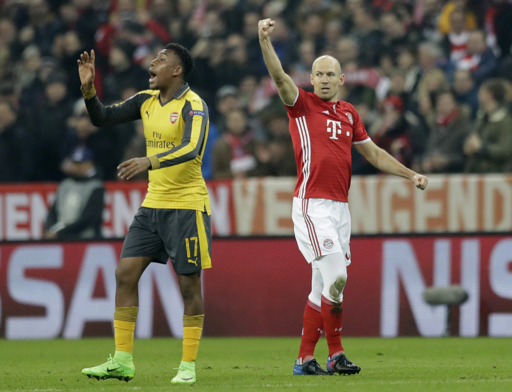 Bayern's Arjen Robben celebrates after scoring the opening goal beside Arsenal's Alex Iwobi, left, during the Champions League round of...
