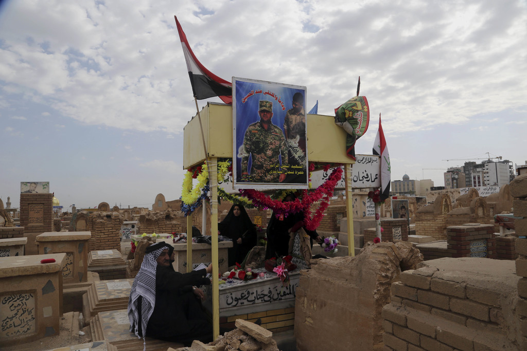 In this Wednesday, Feb. 15, 2017 photo, family members of Iraqi Army officer Hamza Finjan, seen in the poster, Who was killed fighting ...