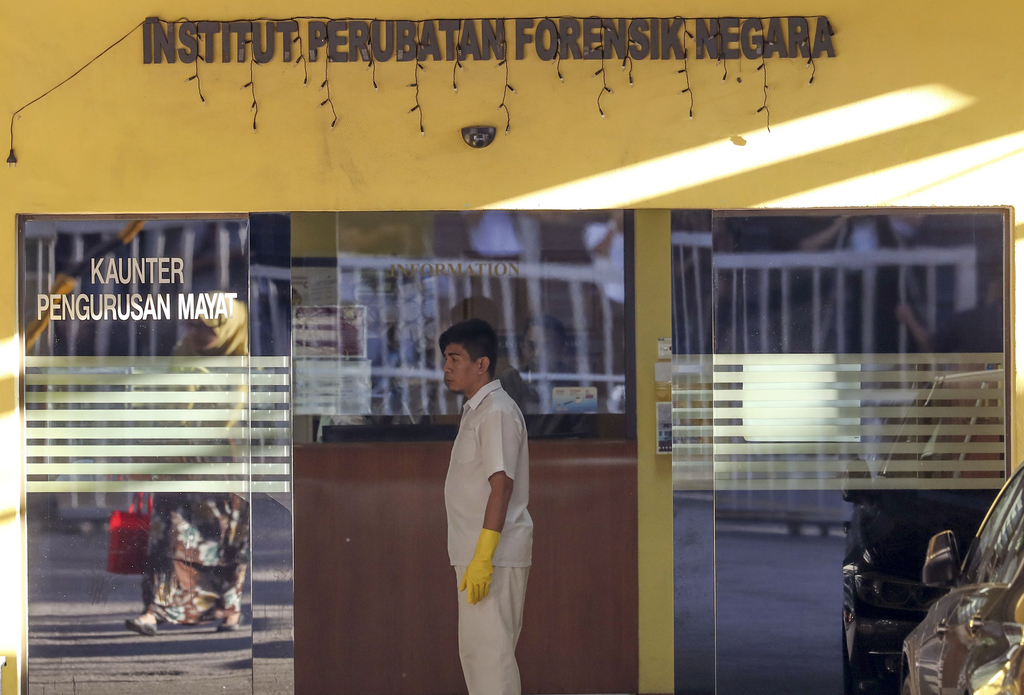 A medical staff member stands at the entrance of the forensic department at a hospital in Kuala Lumpur, Malaysia, Thursday, Feb. 16, 20...