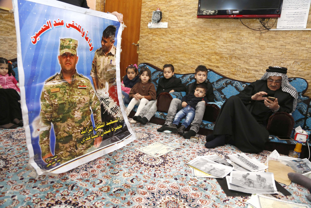 In this Monday, Feb. 6, 2017 photo, Fenjan Jerry Mady, right, the father of Hamza Finjan, an Iraqi officer killed in Mosul fighting Isl...
