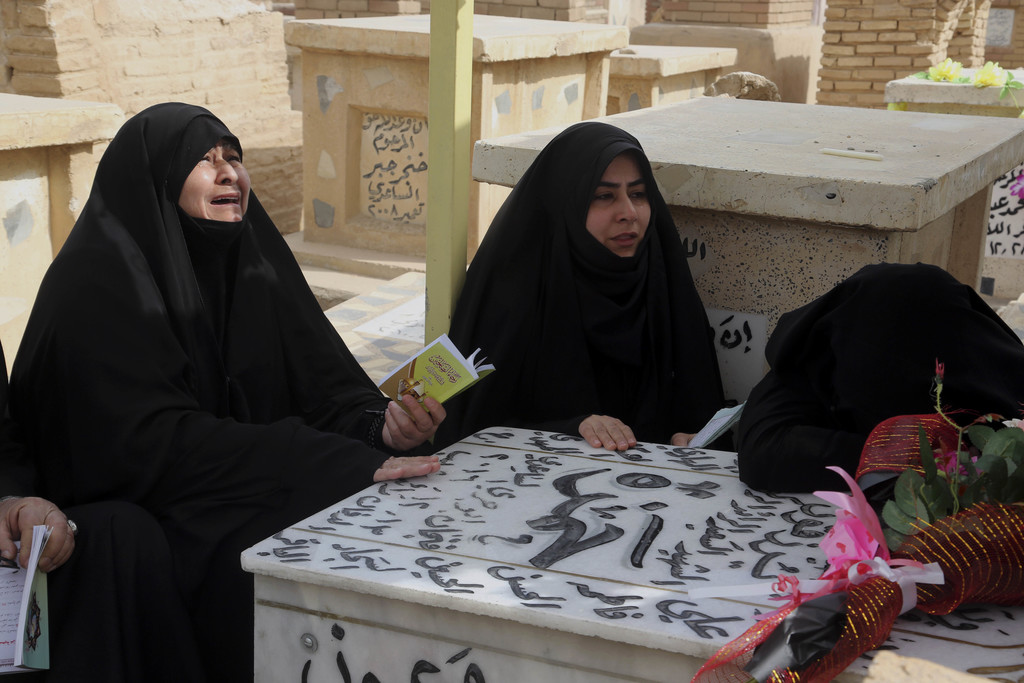 In this Wednesday, Feb. 15, 2017, family members of Iraqi Army officer Hamza Finjan, grieve and pray over his grave in Wadi al-Salam, o...