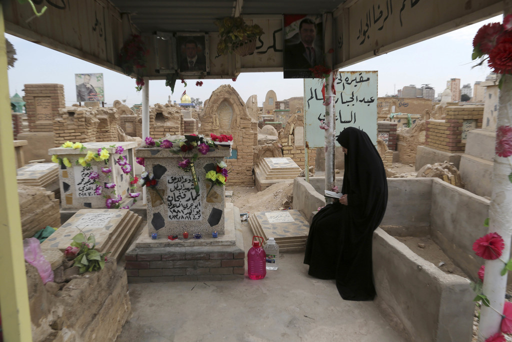 """In this Wednesday, Feb. 15, 2017 photo, the sister of Iraqi Army officer, Hamza Finjan, prays at his grave in Wadi al-Salam, or """"Valley..."""