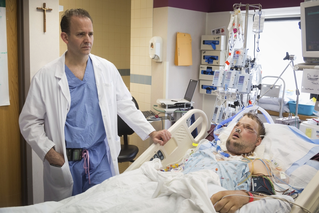 In this June 18, 2016 photo provided by the Mayo Clinic, Dr. Samir Mardini checks on his patient, Andy Sandness, days after leading a t...