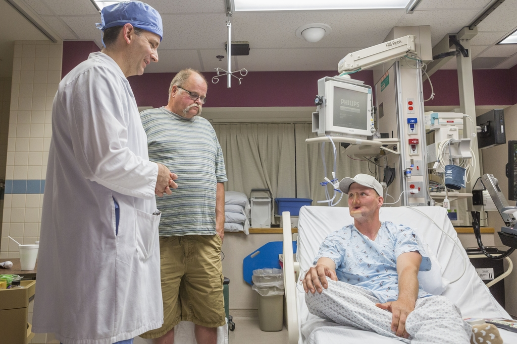 In this June 10, 2016 photo provided by the Mayo Clinic, Andy Sandness, right, talks with his father, Reed Sandness, and Dr. Samir Mard...