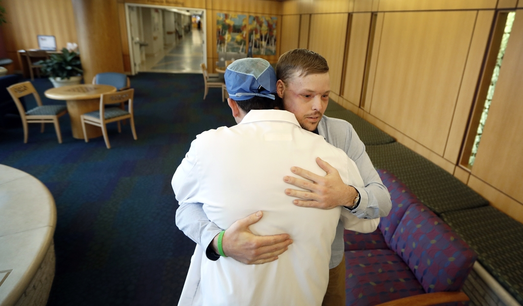 In this Jan. 25, 2017, photo, face transplant recipient Andy Sandness is hugged by Dr. Samir Mardini, foreground, during a visit to the...