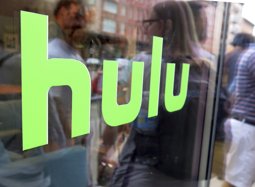 FILE - This June 27, 2015, file photo, shows the Hulu logo on a window at the Milk Studios space in New York. Movie fans can watch a va...