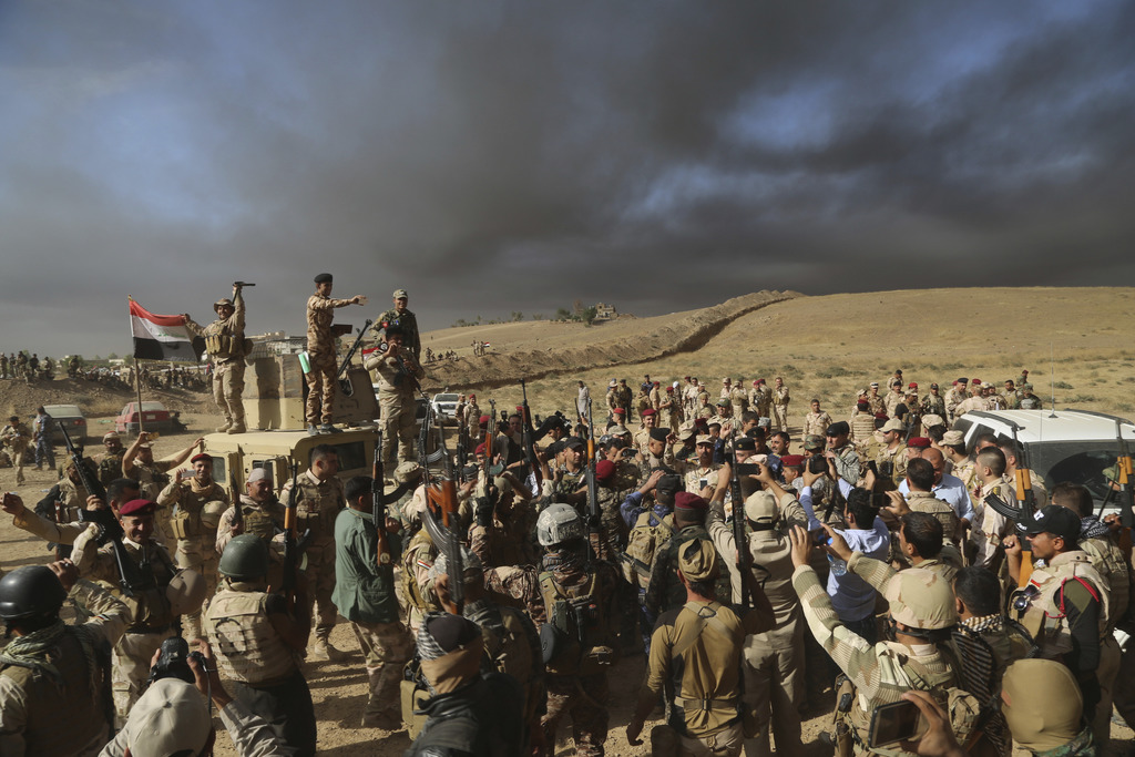 FILE -- In this Oct. 20, 2016 file photo, Iraqi army soldiers raise their weapons in celebration on the outskirts of Mosul, Iraq, . Ira...
