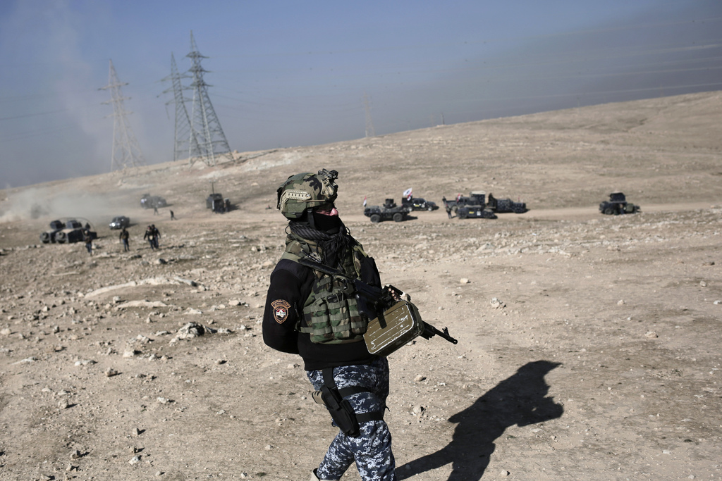 An Iraqi federal police member walks towards the frontline outside the town of Hamam al-Alil, Iraq, Sunday, Feb. 2017. The battle for t...