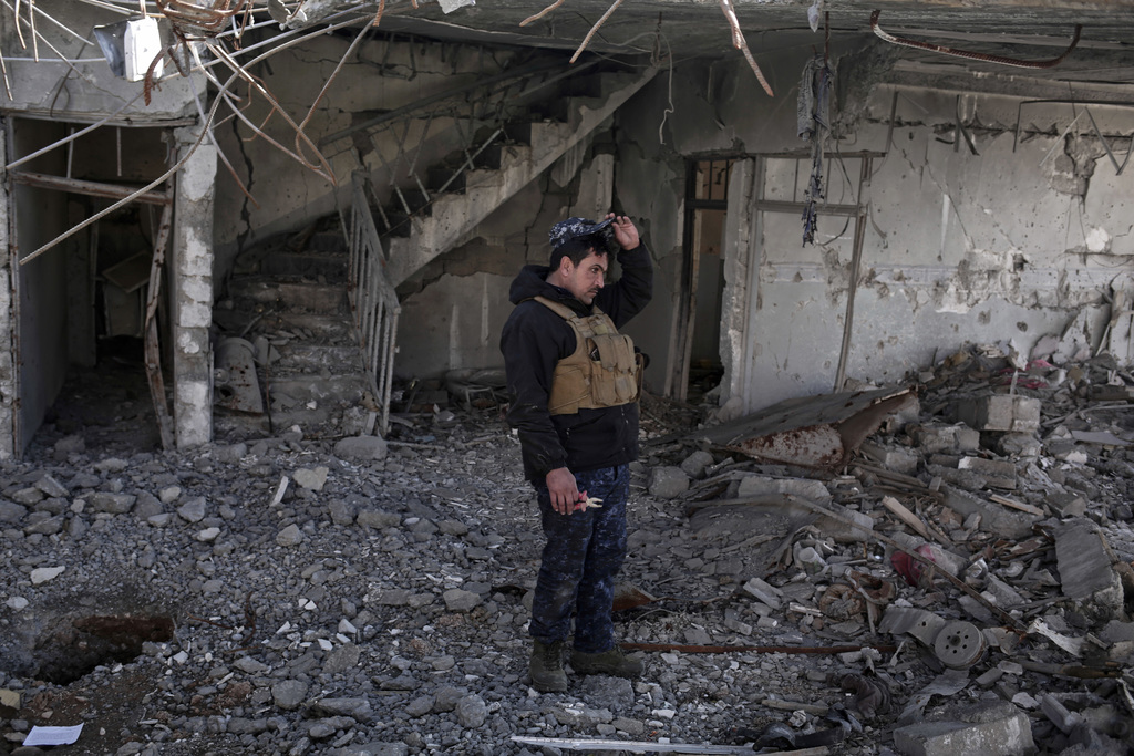 A federal police officer stands inside a damaged house after it was hit by an air strike, in Hamam al-Alil, Iraq, Sunday, Feb. 19, 2017...