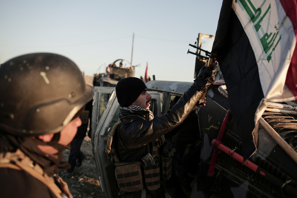 Iraqi federal police forces attach an Iraqi flag to a humvee before going to battle against the Islamic State, in Hamam al-Alil, Iraq, ...