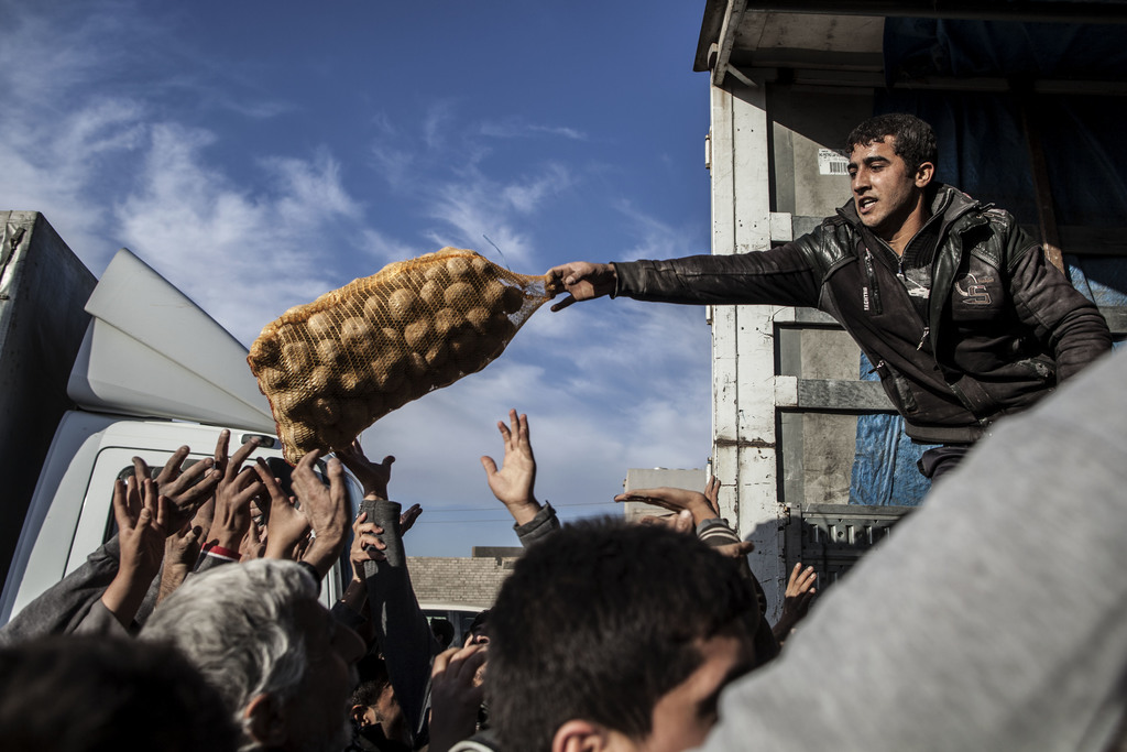 In this Dec. 4, 2016 file photo, an Iraqi man distributes potatoes to civilians in the Samah district of Mosul, Iraq. (AP Photo/Manu Br...