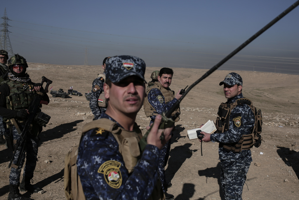 Commanders of the federal police look up after an air strike targeted Islamic State militants, near Hamam al-Alil, Iraq, Sunday, Feb. 1...