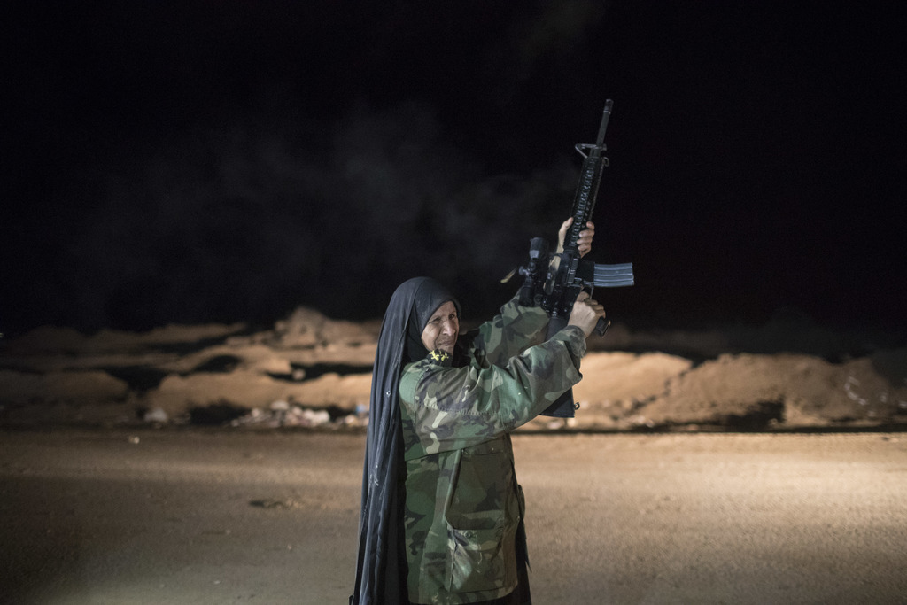 In this Nov. 20, 2016 file photo, a woman fires to the air at a Popular Mobilization Units base south of Mosul, Iraq,. Iraqi troops on ...
