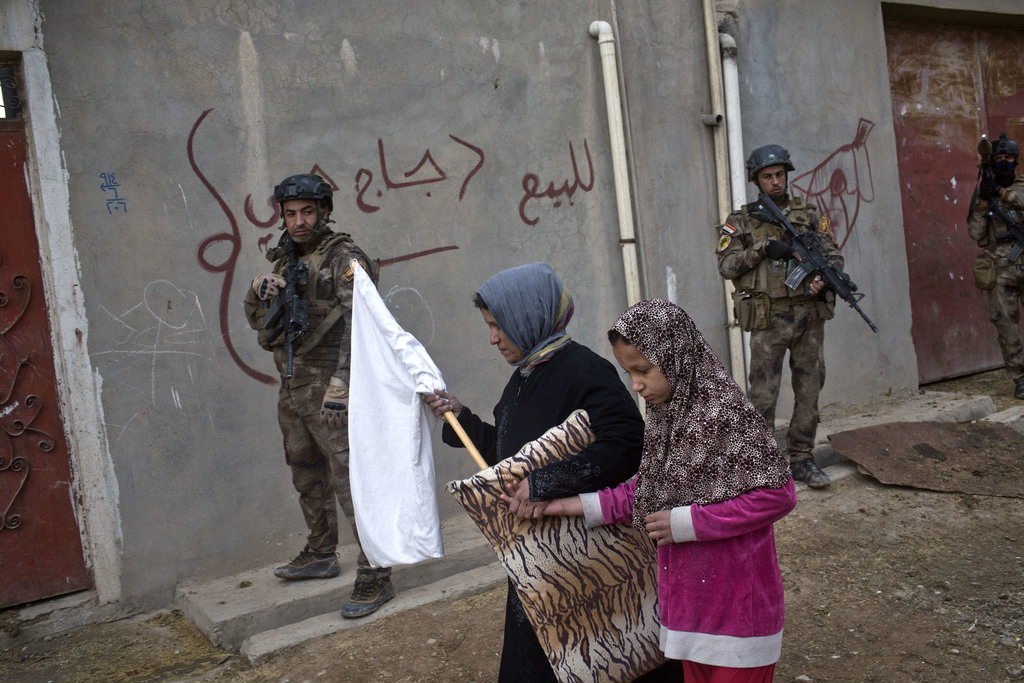 FILE -- In this Nov. 2, 2016 file photo, civilians carry a white flag as they pass by Iraqi special forces on patrol in Gogjali, an eas...