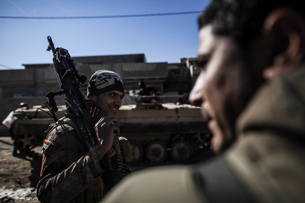 FILE In this Dec. 6, 2016 file photo, an Iraqi soldier from the 9th Infantry Division holds his machine gun while heading to the frontl...