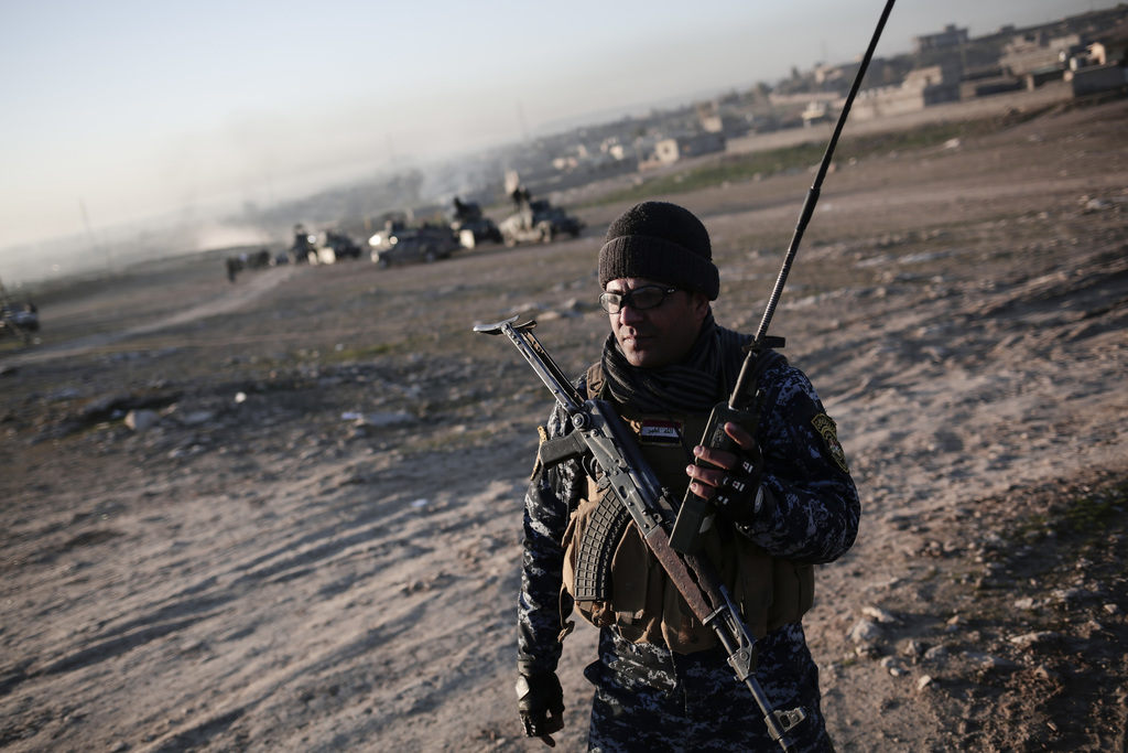 A member of the Iraqi federal police holds a radio in the town of Hamam al-Alil, Sunday Feb. 19, 2017. U.S.-backed Iraqi forces launche...