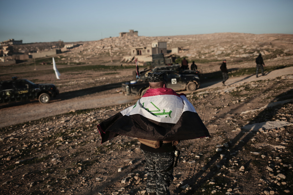A member of the Iraqi federal police wears an Iraqi flag around his shoulders before going to battle against the Islamic State group, i...