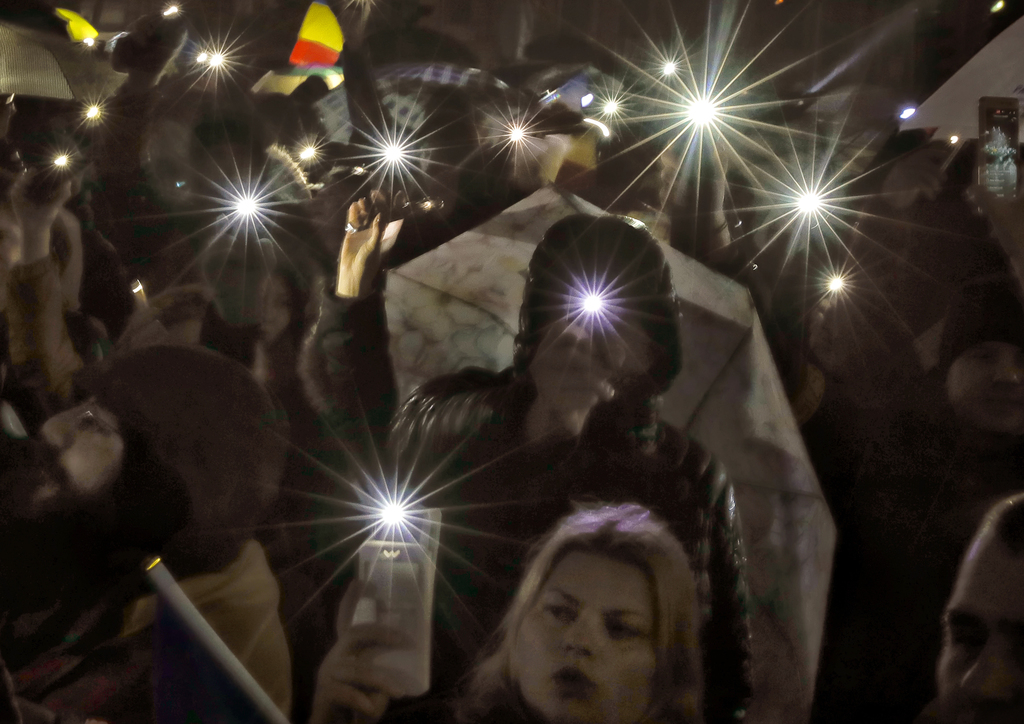 Protesters shine lights of their mobile phones while singing the national anthem outside the government headquarters in the rain in Buc...