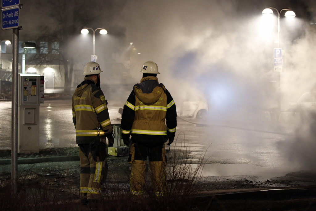 In this picture taken on Monday, Feb. 20, 2017, firefighters survey the scene in the suburb of Rinkeby outside Stockholm. Police in Swe...