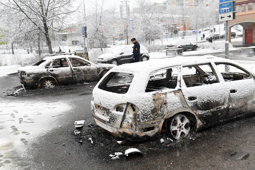 In this picture taken on Monday, Feb. 20, 2017,a policeman investigates a burned out car in the suburb of Rinkeby outside Stockholm. Po...