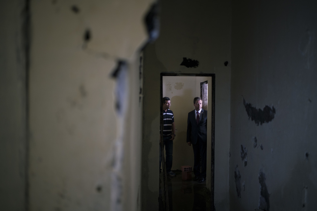 In this Feb. 2, 2017 photo, Claudio Lamachia, head of Brazil's Bar Association, right, stands in a cell where several inmates were kill...