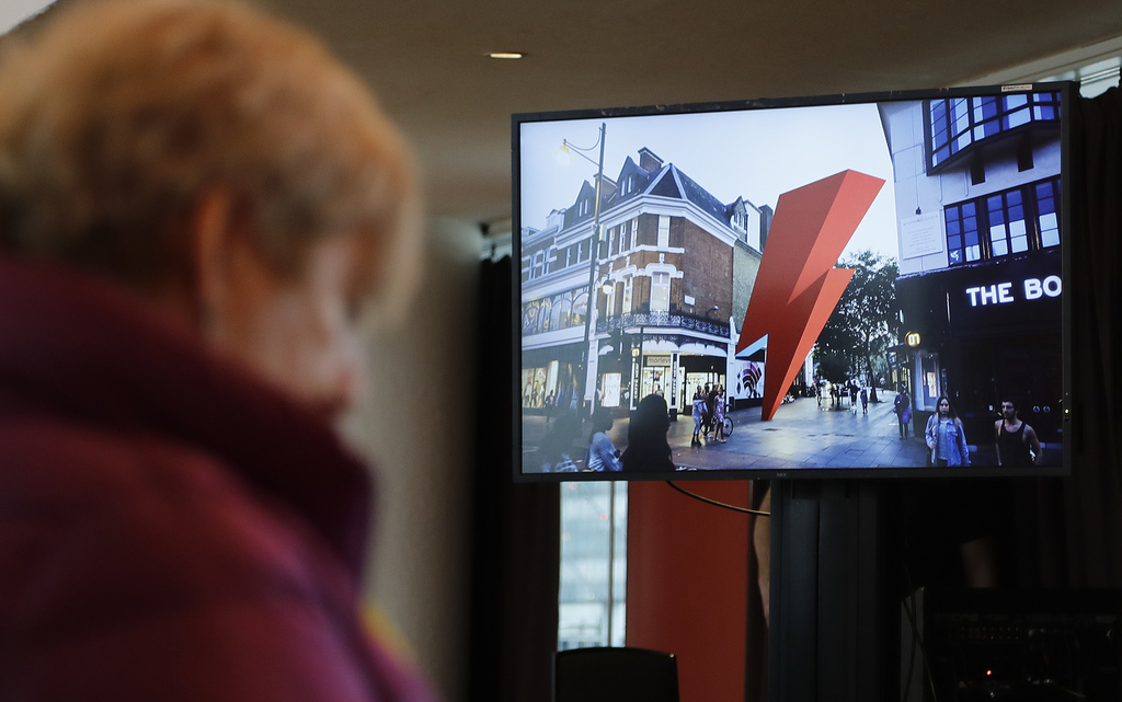 Journalists watch a TV screen that shows the virtual memorial, during a press conference to announce a permanent memorial in Brixton to...