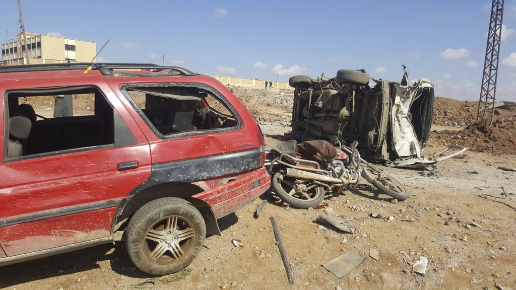 This image released by the Thiqa News Agency, damaged cars after a suicide attacker blew his small pick-up truck outside a security off...