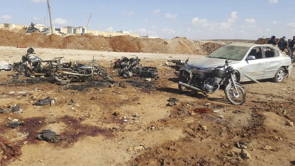 This image released by the Thiqa News Agency, burned motorcycles and car that damaged after a suicide attacker blew his small pick-up t...