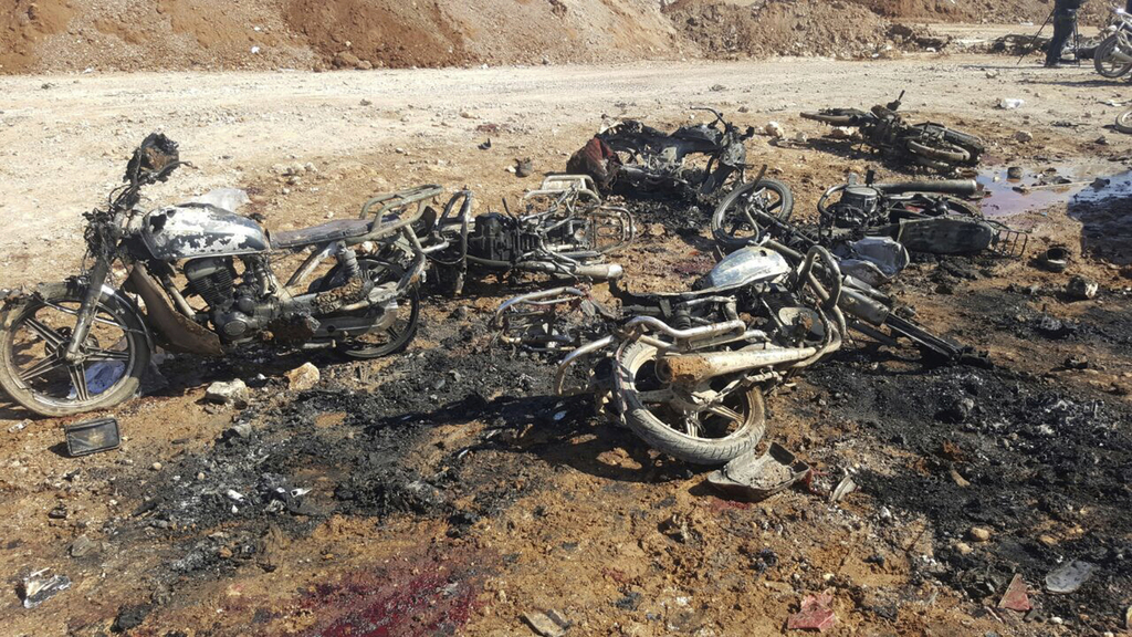 This image released by the Thiqa News Agency, burned motorcycles that damaged after a suicide attacker blew his small pick-up truck out...