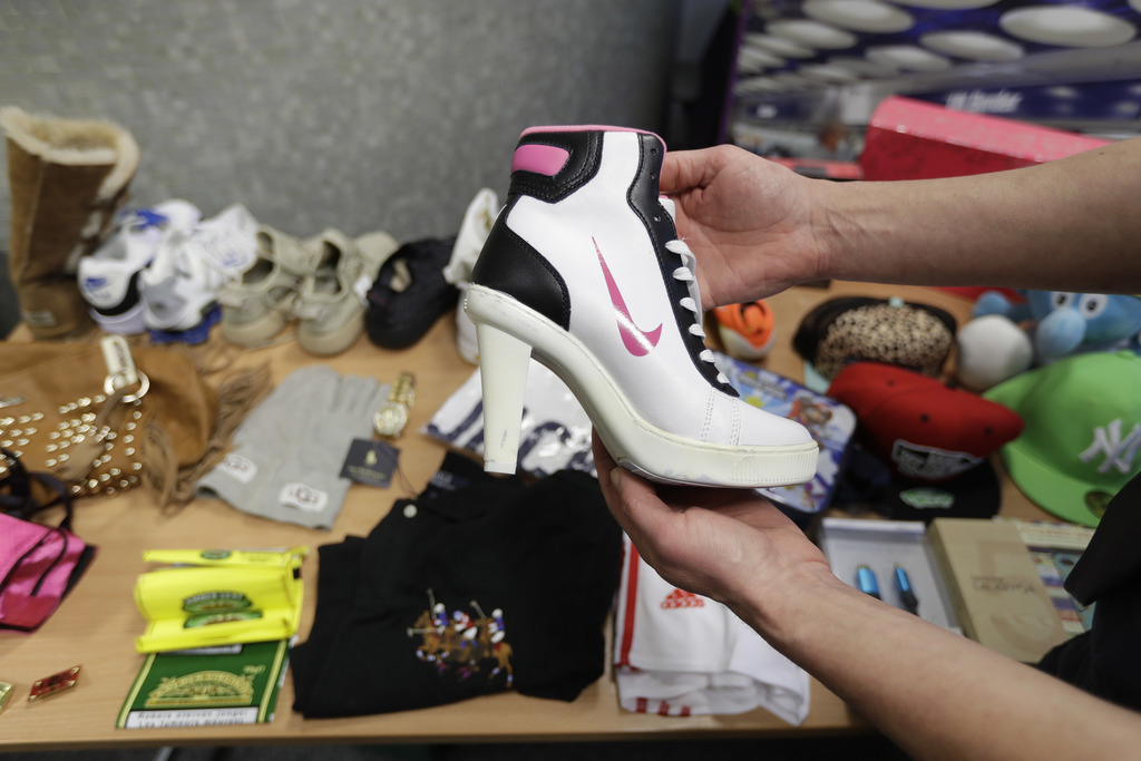In this Wednesday. Feb. 22, 2017 photo, seized counterfeit items, including a fake Nike high heeled shoe, are displayed to be photograp...