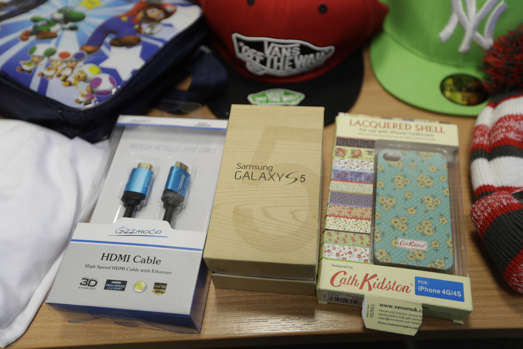 In this Wednesday. Feb. 22, 2017 photo, seized counterfeit items including a packaged fake Samsung Galaxy S5 smartphone are displayed t...