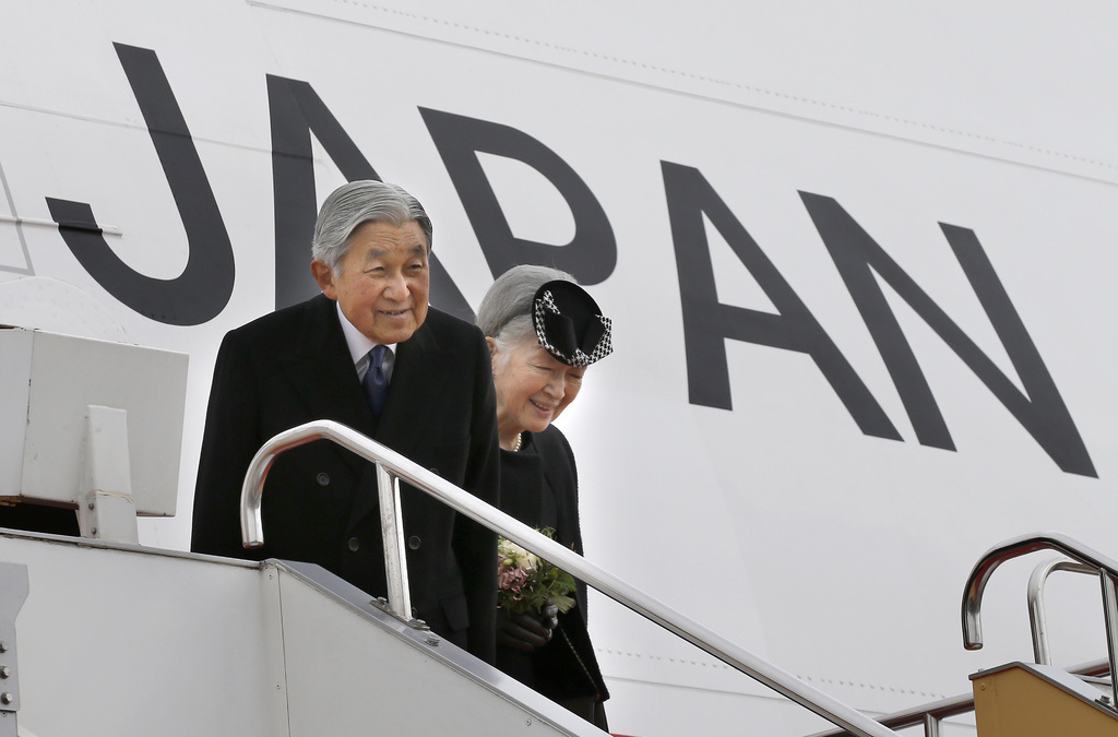 In this Tuesday, Feb. 28, 2017, photo, Japan's Emperor Akihito and Empress Michiko smile as they leave for Vietnam at the Haneda Intern...