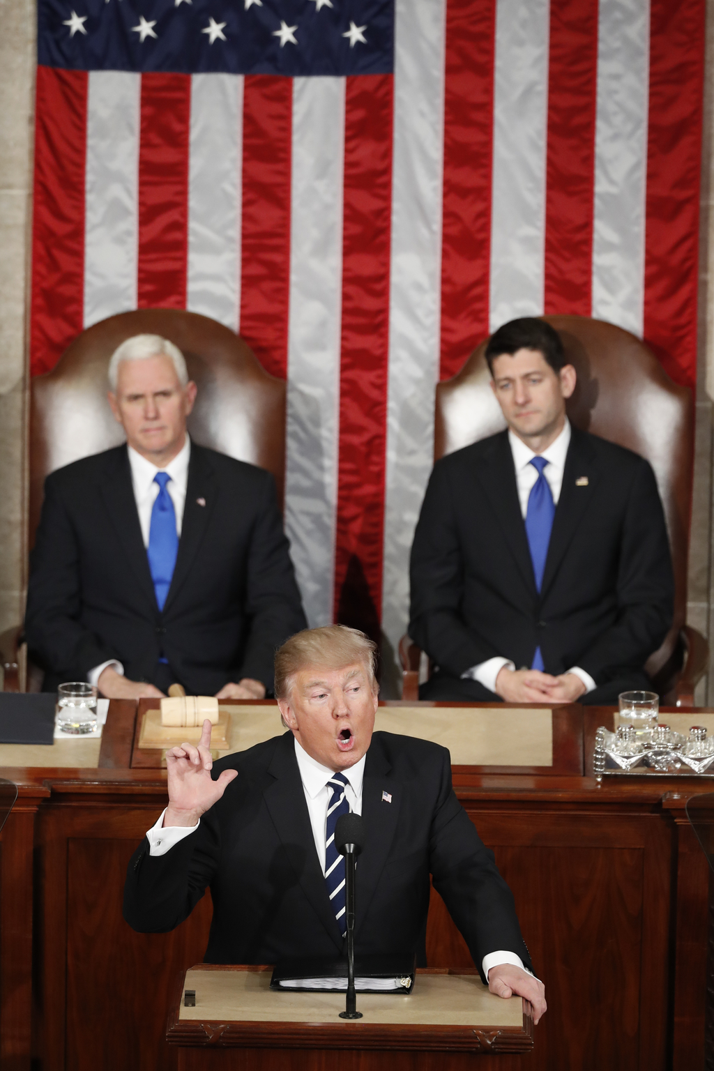 President Donald Trump, flanked by Vice President Mike Pence and House Speaker Paul Ryan of Wis. gestures as he addresses a joint sessi...