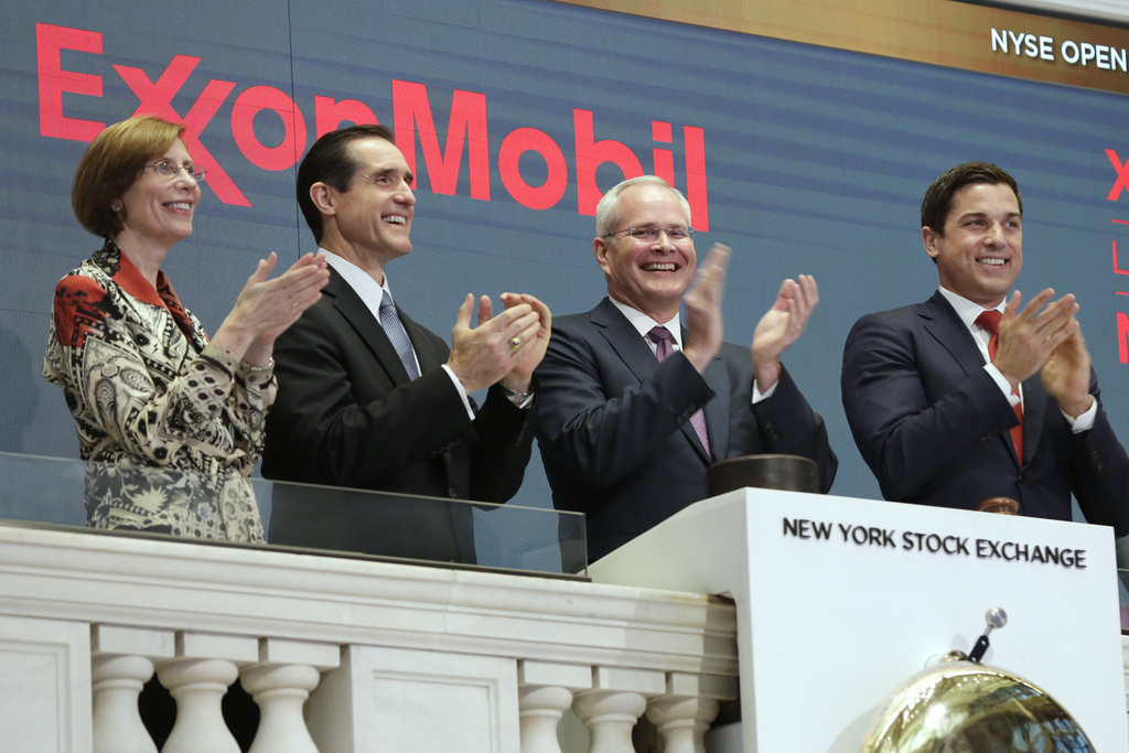 FILE - In this Wednesday, March 1, 2017, file photo, Exxon Mobil Corporation Chairman & CEO Darren Woods, third from left, joins the ap...