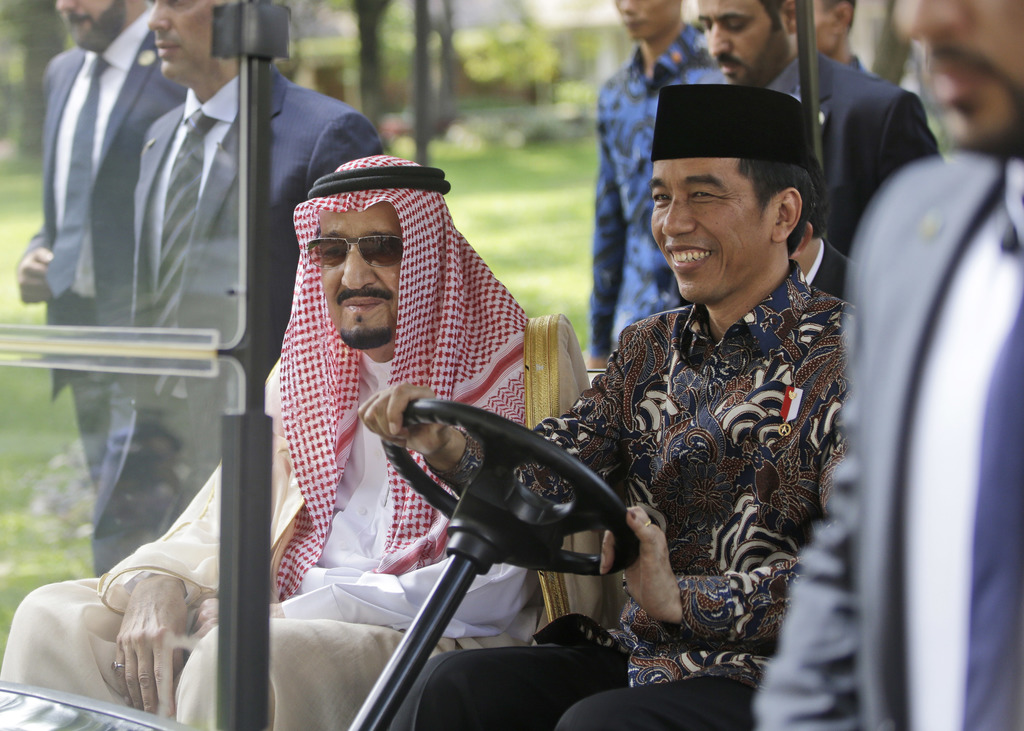 In this Thursday, March 2, 2017, photo, Saudi King Salman, left, rides on a golf cart with Indonesian President Joko Widodo during thei...