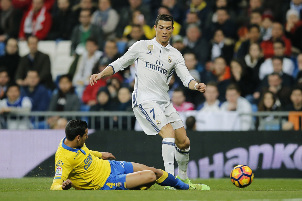 Real Madrid's Cristiano Ronaldo, right, is tackled by Las Palmas Vicente Gomez during a Spanish La Liga soccer match between Real Madri...