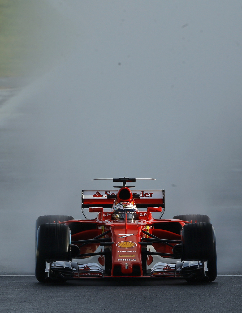 Ferrari driver Kimi Raikkonen of Finland steers his car on a wet track during a Formula One pre-season testing session at the Catalunya...