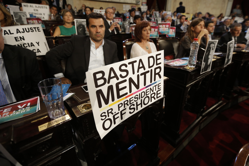"""A sign that reads in Spanish: """"Enough of lying, Mr. President Offshore"""" is seen on the desk of a legislator during Argentina's Presiden..."""