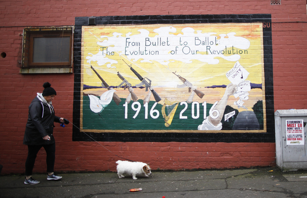 A woman walks her dog past a Republican mural in West Belfast, Northern Ireland, Thursday, March 2, 2017. Voting has begun Thursday in ...