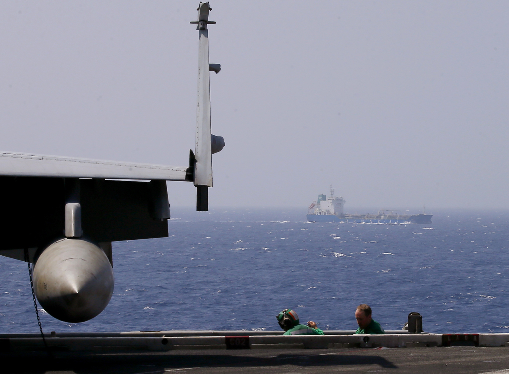 A commercial ship sails across the U.S. Navy aircraft carrier USS Carl Vinson (CVN 70) which is on patrol off the disputed South China ...