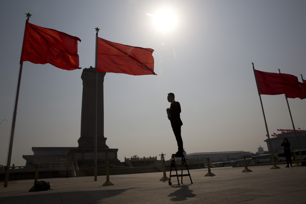 In this Friday, March, 3, 2017, photo, a television anchor stands on a step ladder to report outside the Great Hall of the People where...